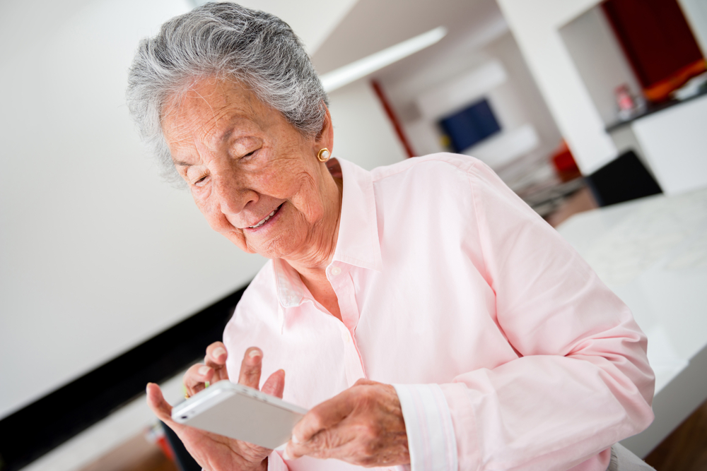 Happy senior woman using app on a cell phone