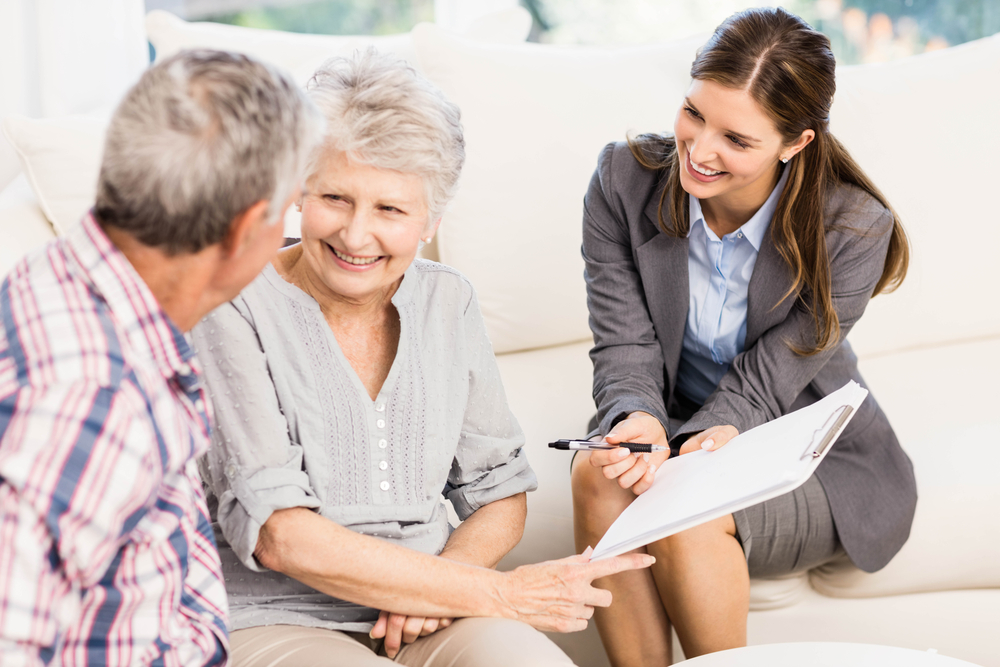 Smiling businesswoman showing documents to senior couple in living room